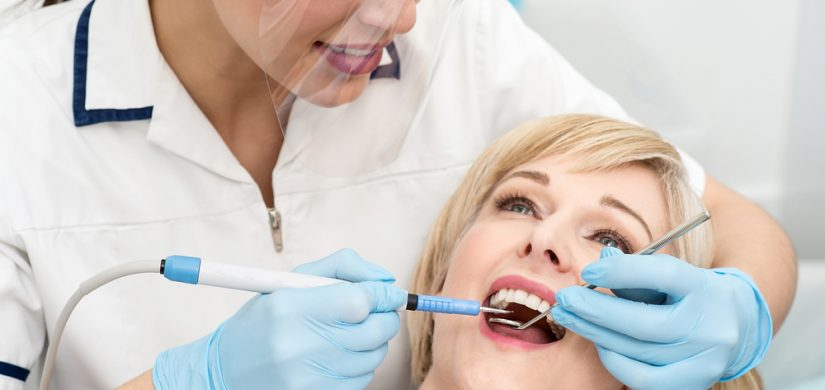Female dentist procedure of teeth cleaning